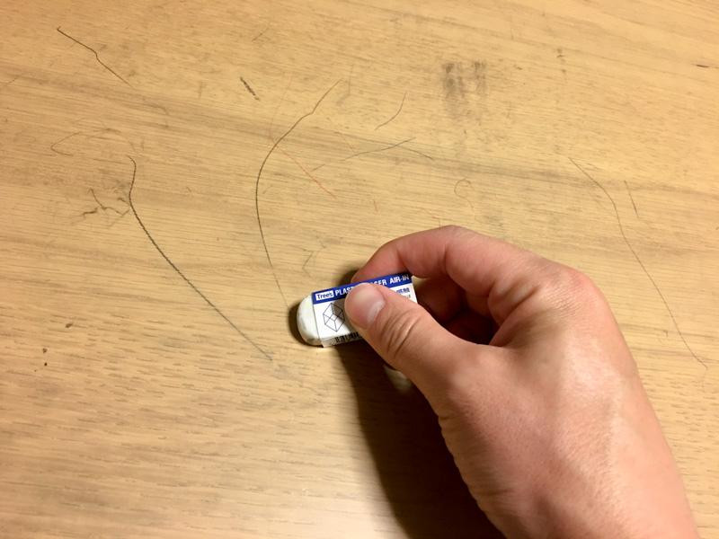 消しゴムで鉛筆汚れを消している