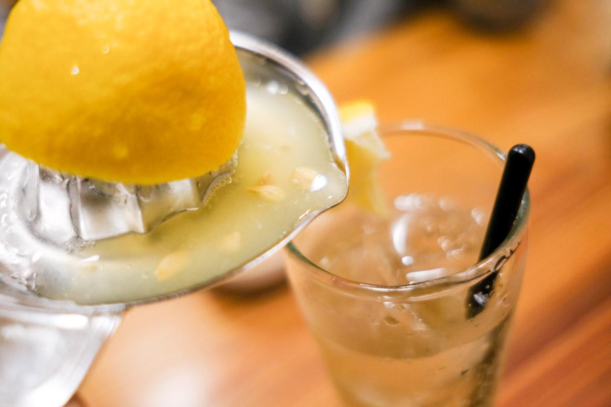 レモンサワーに生搾りレモン果汁を入れているところ