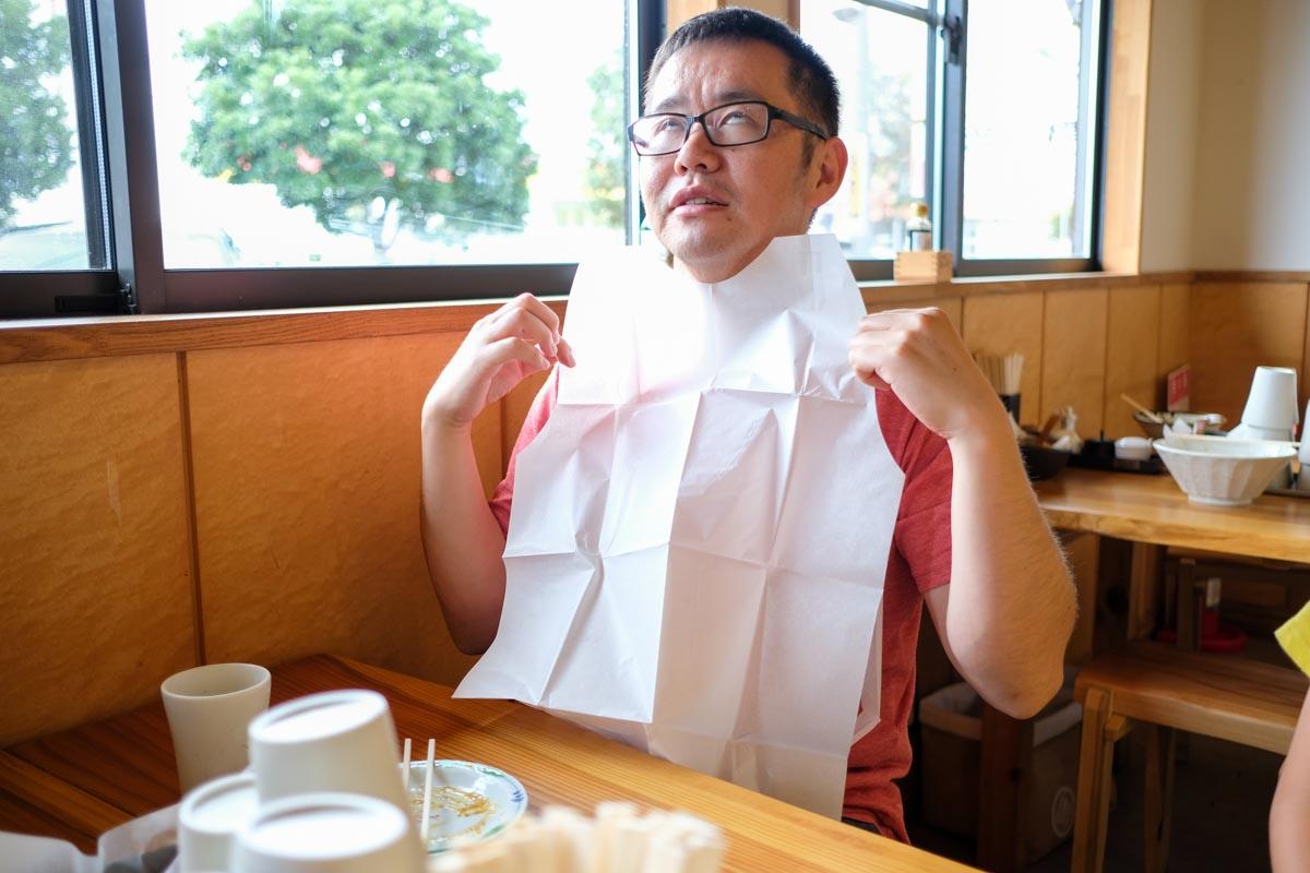カレーうどんを注文した人の紙エプロン