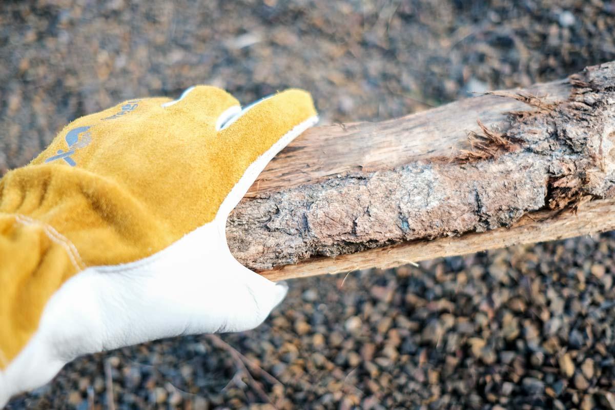 オレゴニアンキャンパーのカウハイドレザーグローブで薪を持っている写真