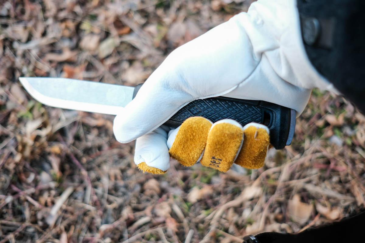 オレゴニアンキャンパーのカウハイドレザーグローブでナイフを持っている写真
